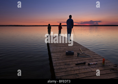A father with his two sons fishing at the end of a wharf on Lake Audy at sunset, Riding Mountain National Park, - Stockfoto