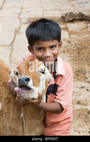 Young indian boy hugging a calf in a rural indian village. Andhra Pradesh, India - Stock Photo