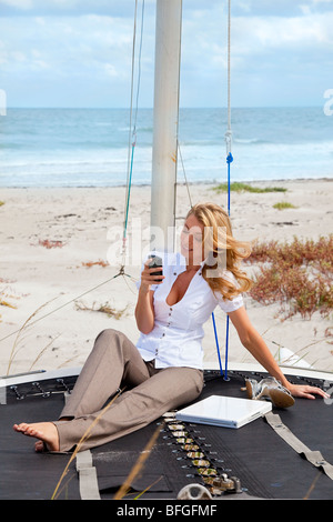 A beautiful young woman sitting barefoot on the deck of a small catamaran sailing boat using her smart phone to - Stock Photo