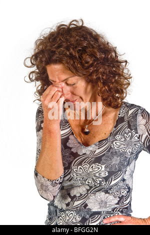 Pinching the bridge of her nose with closed eyes indicates a mood of negative evaluation in this woman. - Stockfoto