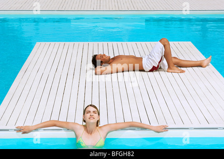 Couple Relaxing at Swimming Pool, high angle view - Stock Photo