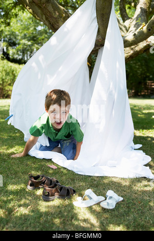 Young boy in back yard crawling out of tent made of bed sheet, portrait - Stock Photo