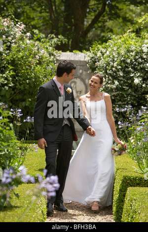 Bride and groom walking in garden, back view - Stock Photo