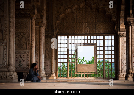An Indian woman sits alone in a temple in Old Delhi, India - Stock Photo