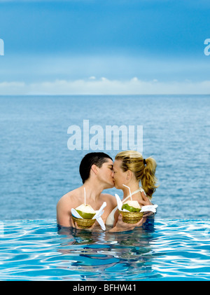 beautiful caucasian couple enjoying their vacation in a beautiful swimming pool by the seaside - Stock Photo
