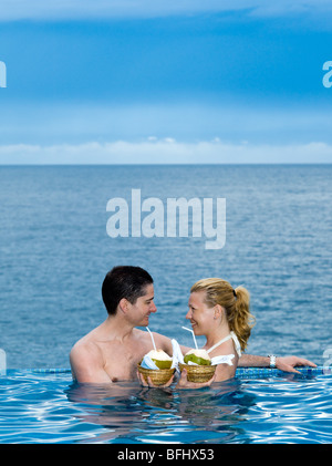 beautiful caucasian couple enjoying their vacation in a swimming pool by the seaside drinking coconut milk - Stock Photo