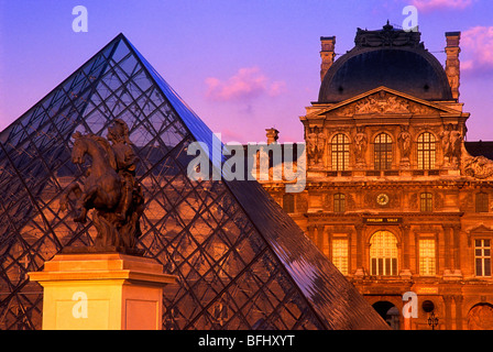 Equestrian statue of King Louis XIV with the Pyramid in the courtyard of the Louvre Museum, Paris, France - Stock Photo