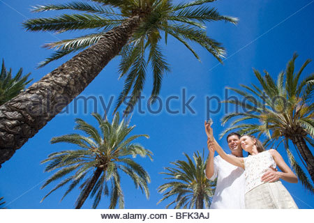 Couple taking self-portrait under palm trees - Stock Photo