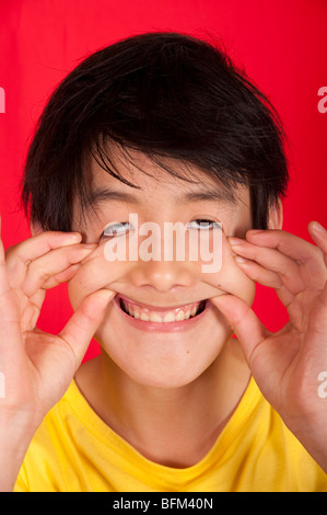 portrait of 13 year old Asian boy with silly face - Stockfoto
