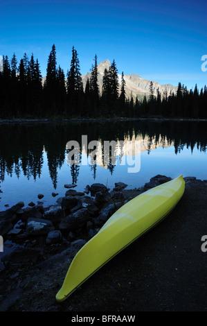 Yellow kayak on shore of Lake O'Hara with Cathedral Mountain, Yoho National Park, BC British Columbia, Canada - Stock Photo