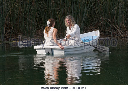 A newlywed couple rowing a boat during their wedding reception. - Stock Photo