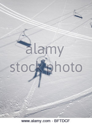 Shadows of people on ski lifts - Stock Photo