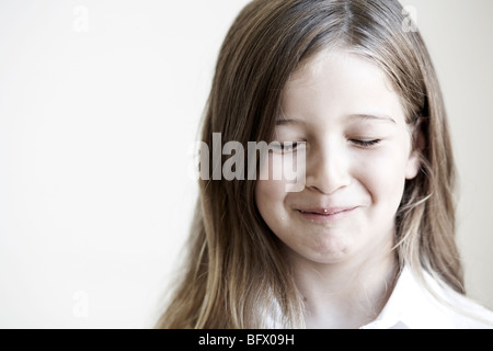 Young girl with crumbs on face - Stock Photo