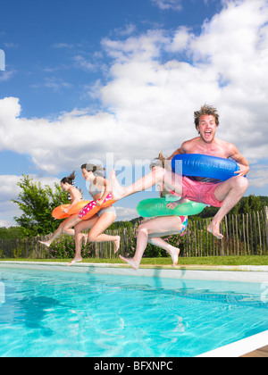 people jumping into pool - Stock Photo