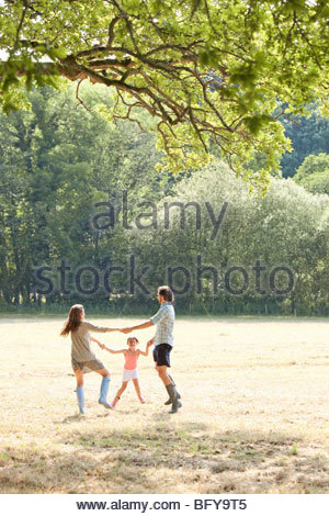 Family playing together in country field - Stock Photo