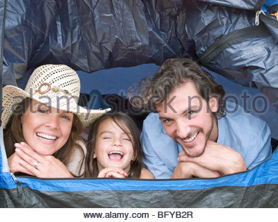 Family lying inside tent laughing - Stock Photo