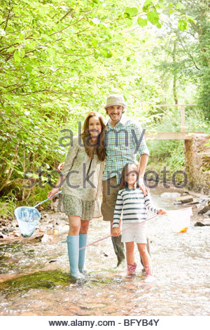 Family standing in country stream - Stock Photo