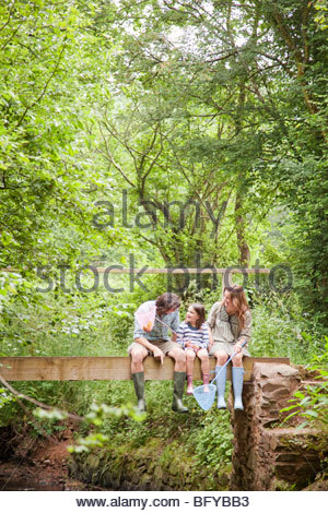 Family sitting talking on country bridge - Stock Photo