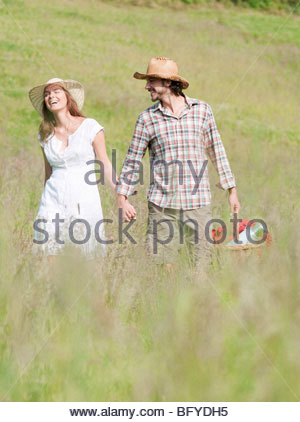 couple in hats walking through meadow - Stock Photo