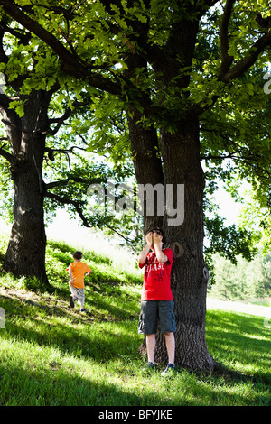 Two Boys Playing Hide and Seek - Stock Photo