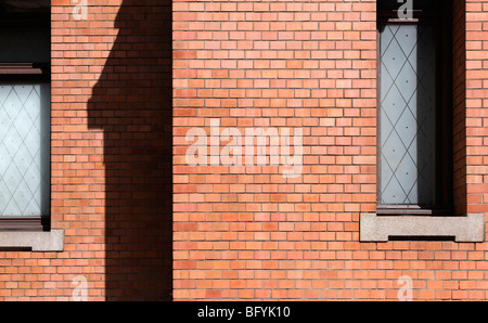 Red brick wall with windows - Stock Photo
