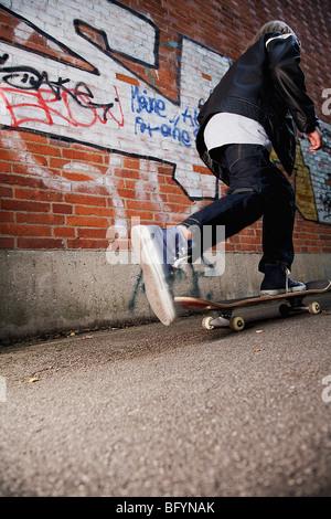 rear view of young boy skateboarding along wall - Stock Photo