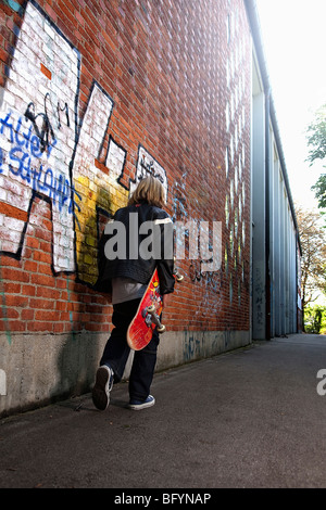 rear view of young boy walking along wall with skatebord - Stockfoto