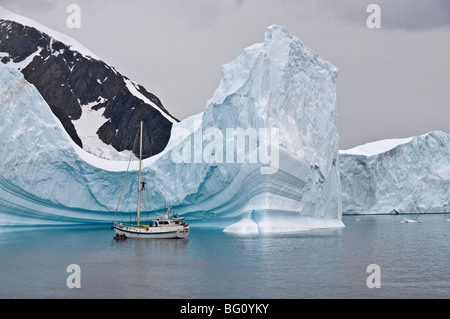 Sailing yacht and iceberg, Errera Channel, Antarctic Peninsula, Antarctica, Polar Regions - Stock Photo