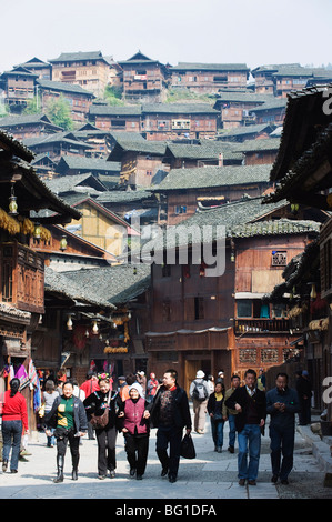 Tourists walking by wooden houses on the old streets of Xijiang, Guizhou Province, China, Asia - Stock Photo