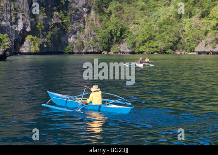 Fishermen in their outrigger boats off the cliffs that characterise the coast of Coron Island and create a rich - Stock Photo