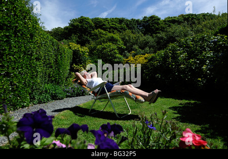 OLD  AGE LADY PENSIONER ENJOYS RETIREMENT SUNBATHING IN BRITISH GARDEN UK - Stockfoto