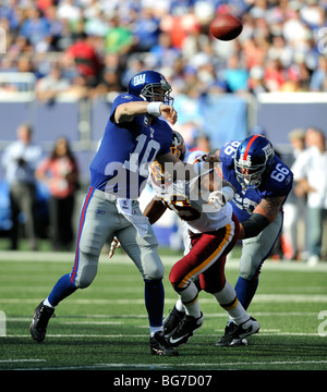 Eli Manning of the New York Giants gets the pass away while under pressure from the Washington Redskin defense - Stock Photo