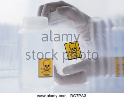 Scientist holding bottle with toxic label - Stock Photo