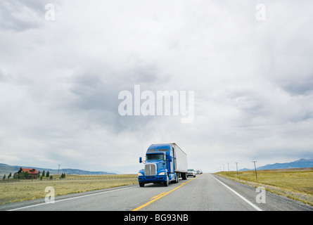 A semi truck on a lonely highway in Montana, USA. - Stock Photo