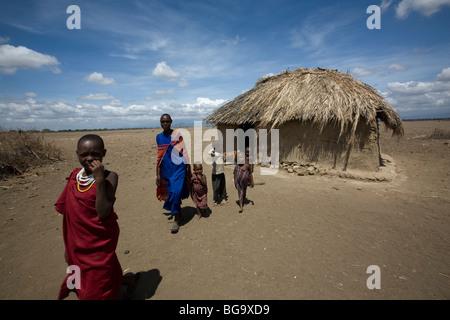 A Maasai family exits their house in the village of Tindagani, Kilimanjaro Region, Tanzania, East Africa. - Stock Photo
