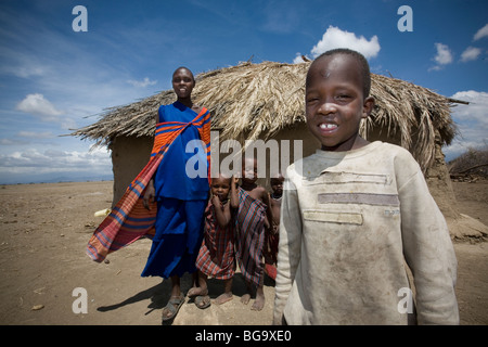 A Maasai family stands in front of their house in village of Tindagani, Kilimanjaro Region, Tanzania, East Africa. - Stock Photo