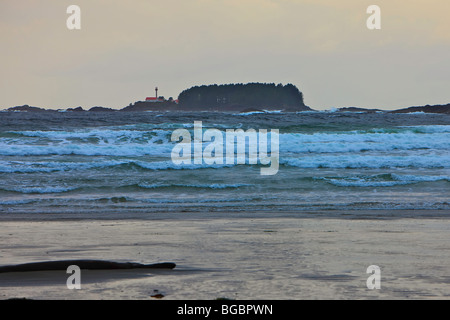 Stormy waves of the Pacific Ocean at the beach in Cox Bay near Tofino with the Lennard Island Lighthouse in the - Stock Photo