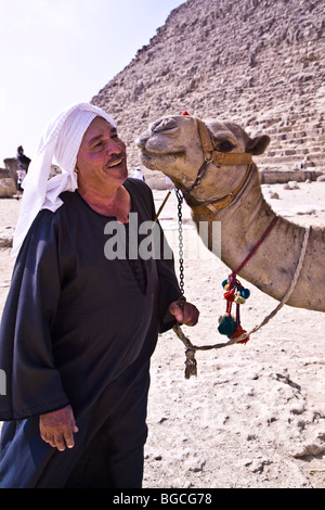A man and his camel (and there is a great deal of affection) at the Pyramids of Giza near Cairo Egypt - Stock Photo