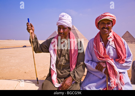 Two Egyptian male camel drivers who give camel rides at the Pyramids of Giza near Cairo Egypt - Stock Photo
