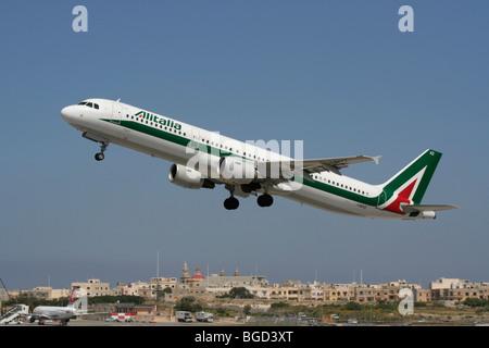 Air travel. Alitalia Airbus A321 passenger jet plane taking off from Malta - Stock Photo
