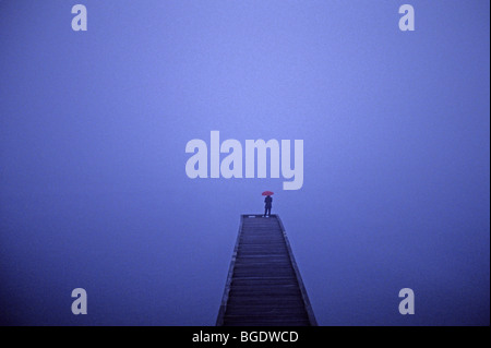 Lake Washington at sunrise in fog with single woman on a long dock holding a red umbrella - Stockfoto