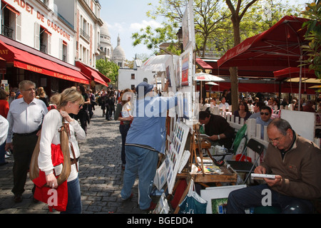 Tourists browse artist stalls at Place du Tertre in Montmartre, Paris, France - Stock Photo