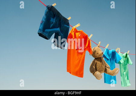 Childrens clothes and teddy bear on a washing line against a blue sky. India - Stock Photo