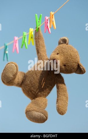 Teddy bear hanging from a washing line against a blue sky. India - Stock Photo