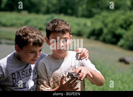 8 year-old children examine wild Eastern Painted Turtle (Chrysemys picta picta). Pennington, New Jersey - Stock Photo