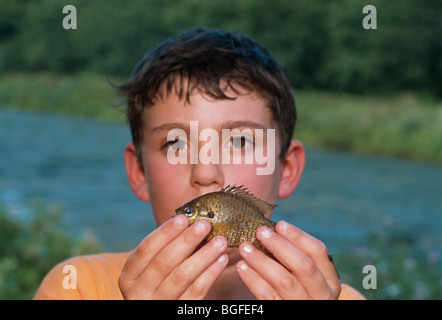 8 year-old boy holding a Pumpkinseed Sunfish (Lepomis gibbosus) at the Watershed Pond. Pennington, New Jersey - Stock Photo
