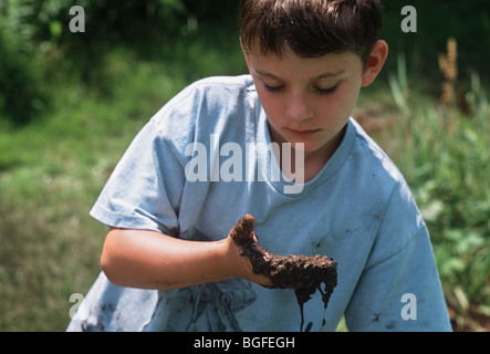 8 year-old child examines creatures in mud at Watershed Pond. Pennington, New Jersey - Stock Photo