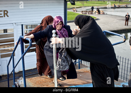 Old Muslim women getting aboard boat ferry in Istanbul, Turkey - Stock Photo