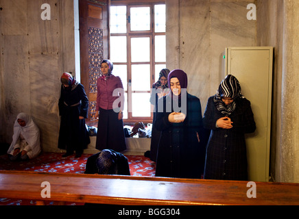 Muslim women praying in Blue Mosque Sultan Ahmet Mosque in Istanbul, Turkey - Stock Photo