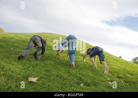 three boys having a race, climbing up a grassy hill on all fours - Stock Photo